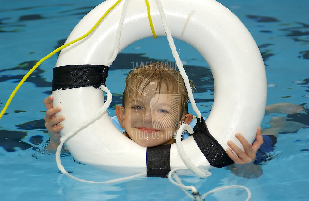 boy in pool with lifesaver