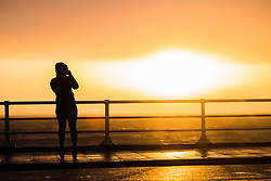 ©Licensed to London News Pictures. 26/04/2019 <br /> A woman takes a photo as the sun briefly emerges from behind the dark clouds , while the choppy seas foretell the arrival of Storm Hannah, the latest named storm of the 2019 season. With winds expecting to gust at between 60 and 70mph overnight, there is a risk of damage to property and injuries. The Met Office has issued a yellow warning for strong winds covering much of the south if the UK from this evening until mid afternoon tomorrow. Photo credit Keith Morris/LNP