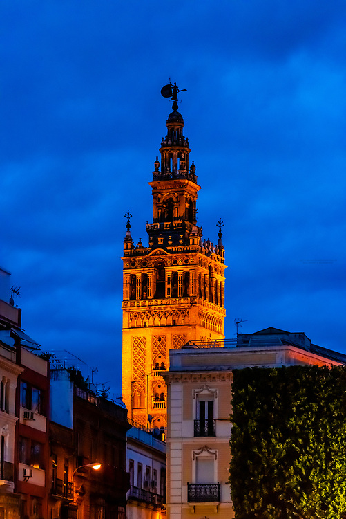 The Giralda Tower illuminated at twilight, Seville, Andalusia, Spain.