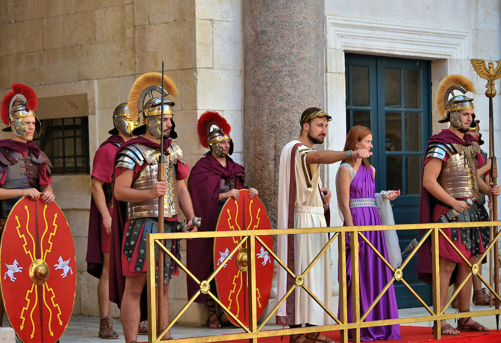Roman Emperor Surrounded by Soldiers Near Vestibule in Split, Croatia <br /> From 32 BC until 480 AD, Salona was the capital of the Roman province of Dalmatia. It was also the birthplace of Roman Emperor Diocletian. This is why he built his retirement palace nearby in Spalatum which is today&rsquo;s Split. If during your visit you hear lots of trumpets and fanfare near the Peristyle, then rush to see the emperor&rsquo;s greeting. He emerges from his private quarters at the Vestibule and onto an elevated platform called the Protyron.  He and the empress are surrounded by soldiers wearing centurion helmets, the traditional military headgear from 100 BC until 300 AD. The performance is brief but entertaining.