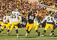 November 23 2013: Michigan Wolverines kicker Matt Wile (45) gets off a kick as Iowa Hawkeyes defensive lineman Louis Trinca-Pasat (90) closes in during the first quarter of the NCAA football game between the Michigan Wolverines and the Iowa Hawkeyes at Kinnick Stadium in Iowa City, Iowa on November 23, 2013. Iowa defeated Michigan 24-21.