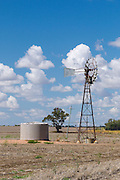 Windmill and water tank in dry cropping farm paddock under cumulus clouds in Clermont, Queensland, Australia. <br />