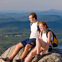 A young couple takes a break from hiking on the summit of Mount Monadnock in New Hampshire's Monadnock State Park.