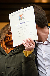 © Licensed to London News Pictures. 31/12/2019. London, UK. Rebecca Steinfeld and Charles Keidan kiss behind their civil partnership certificate as they ;eave Kensington and Chelsea registry office in London, following a mixed sex union ceremony. The couple took their fight to the Supreme Court to allow civil partnerships between heterosexual couples. Photo credit: Ben Cawthra/LNP