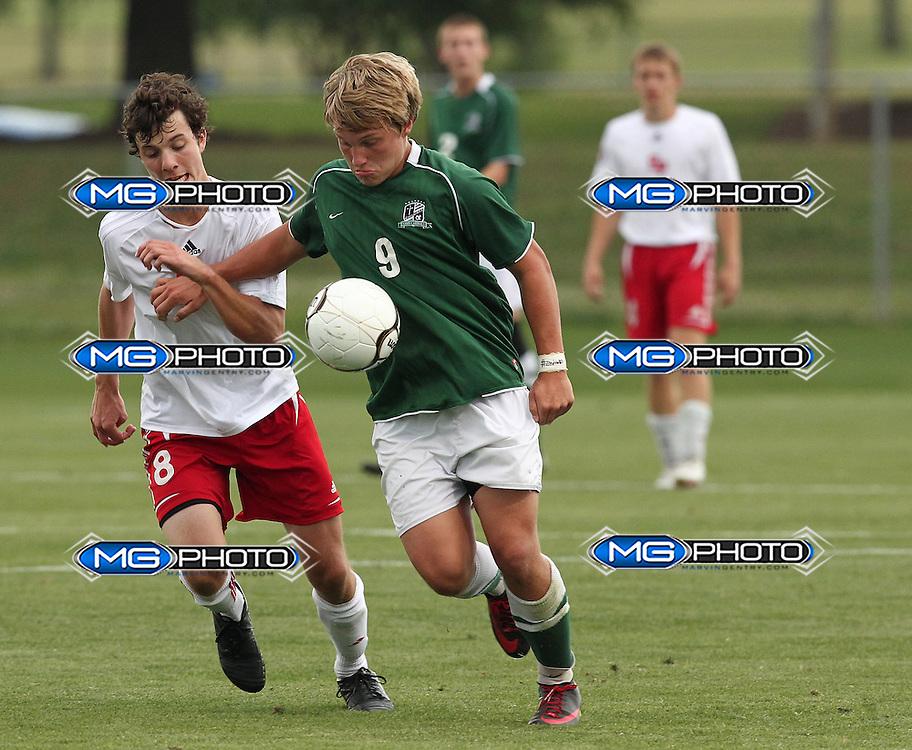 May 12, 2012; Huntsville, AL, USA;  John Carroll's Reece Holcombe (9) controls the ball from St. Paul's Jonathan Ashley (8). Mandatory Credit: Marvin Gentry