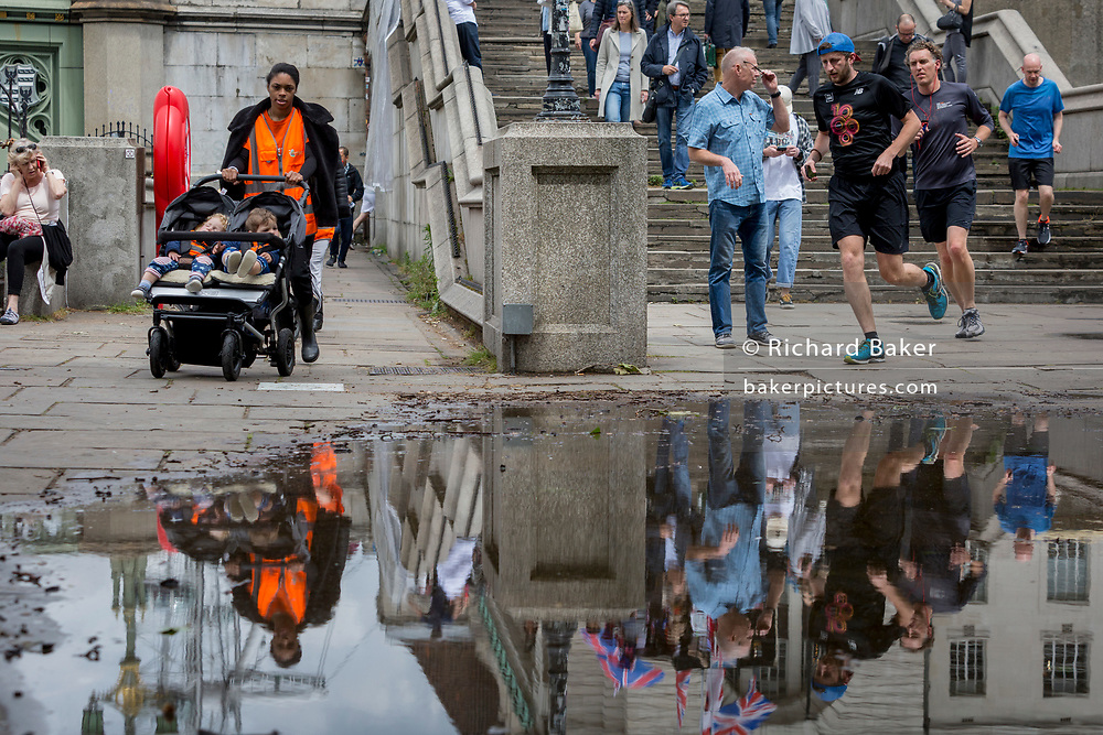 After heavy rainfall the day before, a childminder and runners are reflected in a puddle on the Albert Embankment on the Lambeth side of Westminster Bridge, on 11th June 2019, in London, England.