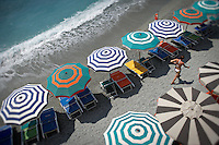 Colorful striped umbrellas and chairs line the beach in Monterosso, Italy.