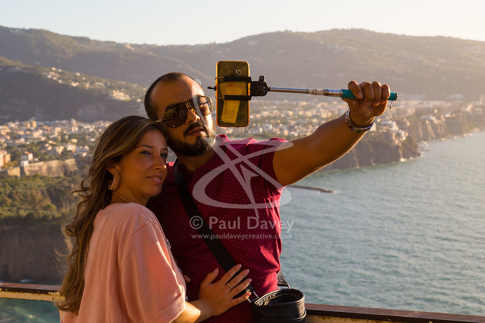 Sorrento, Italy, September 17 2017. A couple take pictures with a smartphone overlooking Sorrento, Italy. © Paul Davey