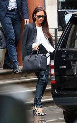 Fashion designer Victoria Beckham seen leaving her new London clothes store, that is due to open at the end of summer 2014. Carrying a mini tote bag from her own VB Collection, the mother of four looked immaculate, wearing designer sunglasses, topped with a black blazer over a draped blouse, skinny jeans and Manolo Blahnik BB Leopard-Print Pony Hair Pumps -  shoes. London. UK. 14/08/2014<br />