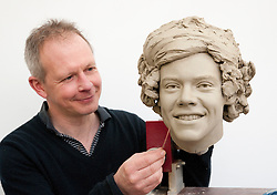 """© Licensed to London News Pictures. 15/02/2013. London, UK Sculptor Jim Kemp works on the clay head of Harry Styles. Madame Tussauds today released pictures of sculptors working on the life-like clay heads of the five members of pop band """"One Direction ' The clay heads will be used to create the moulds for their new wax figures. Niall, Liam, Louis, Harry and Zayn have been closely involved in the creation process giving the creative team two sittings at which hundreds of measurements were taken to ensure total accuracy. The clay heads will now be used to make the moulds for the final wax figures, which will be revealed in London. Photo credit : Madame Tussauds /LNP"""