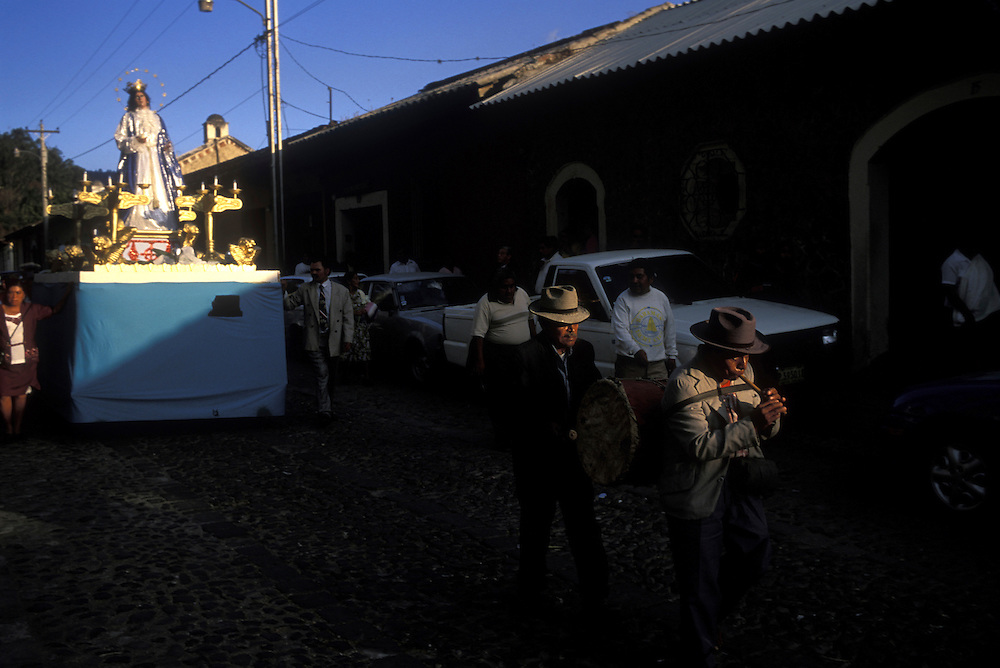 Guatemala, Antigua, Religious procession winds through cobblestone downtown streets on Sunday afternoon