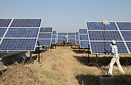 Workers clean solar panels at Azure Solar Plant in Khadoda in Gujarat state in India on Dec 15, 2011.<br /> India plans to generate 1,000 MW of power by 2013 as the county, with growing economy with a surging middle class, is facing a severe electricity deficit that often runs between 10 and 13 percent of daily need.<br /> (Photo by Kuni Takahashi)