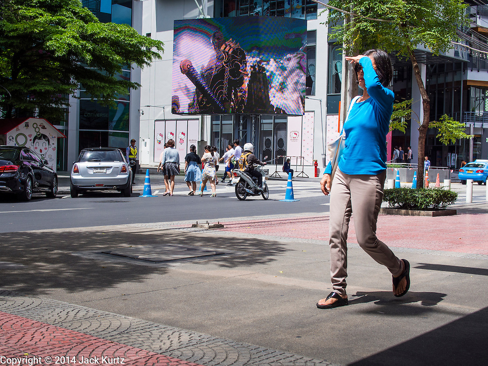 15 JULY 2014 - BANGKOK, THAILAND: A woman walks through Siam Square, a shopping and entertainment area in Bangkok. There is a range of shops and services, including tutor schools, restaurants, cafe, designer clothing boutiques, record stores, bookshops, Hard Rock Cafe and banks in the area. Siam Square is owned by Chulalongkorn University and is managed by its Property Management Office, known as the Chula Property.    PHOTO BY JACK KURTZ