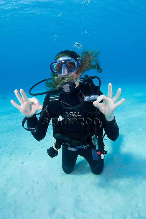 Diver kneeling on sandy sea floor, making silly poses with mask over hair, profile, Vaavu Atoll, The Maldives