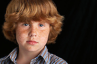 Boy (10-12) on black background portrait close-up