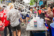 14 APRIL 2013 - BANGKOK, THAILAND:  A woman throws water at passers by on April 14, 2013 in Bangkok, Thailand. The Songkran festival is celebrated in Thailand as the traditional New Year's Day from 13 to 15 April. The throwing of water originated as a way to pay respect to people and is meant as a symbol of washing all of the bad away. PHOTO BY JACK KURTZ