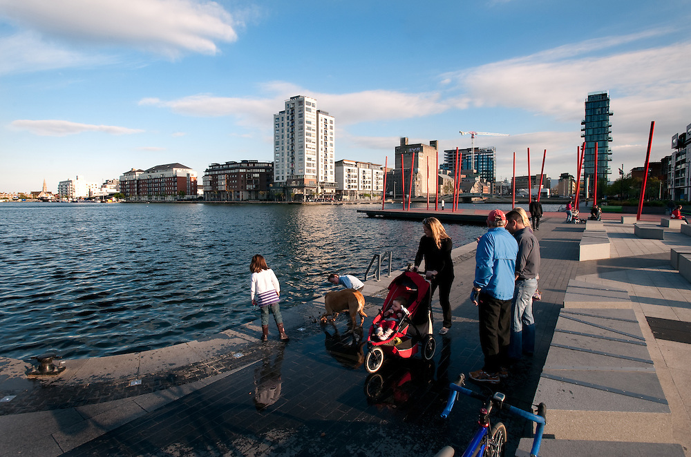 People walking along the regenerated Grand Canal basin in Dublin's docklands area.