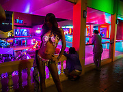 "05 JANUARY 2012 - BANGKOK, THAILAND: A sex worker poses for photos in the Nana Entertainment District in Bangkok. Prostitution in Thailand is technically illegal, although in practice it is tolerated and partly regulated. Prostitution is practiced openly throughout the country. The number of prostitutes is difficult to determine, estimates vary widely. Since the Vietnam War, Thailand has gained international notoriety among travelers from many countries as a sex tourism destination. One estimate published in 2003 placed the trade at US$ 4.3 billion per year or about three percent of the Thai economy. It has been suggested that at least 10% of tourist dollars may be spent on the sex trade. According to a 2001 report by the World Health Organisation: ""There are between 150,000 and 200,000 sex workers (in Thailand).""      PHOTO BY JACK KURTZ"