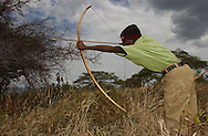Yaeda Valley, Tanzania: Kaunda, a Hadzabe man, practices hunting in a manner relatively unchanged for 90,000 years. The Hadzabe are one of the last remaining tribes of hunter gatherers on earth, and are currently threatened by a deal that cedes hunting rights on their tribal land to a company of United Arab Emirates princes. The tribe, which numbers fewer than 1500, have adopted aspects of the modern world, slowly. Kaunda says he prefers his khakis and ski cap these days to the traditional Hadzabe animal skins. (PHOTO: MIGUEL JUAREZ LUGO)