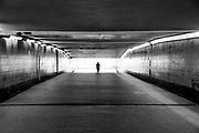 Een man loopt alleen door een donkere tunnel. Zijn silhouet steekt af tegen het licht erbuiten.Foto: Flip Franssen
