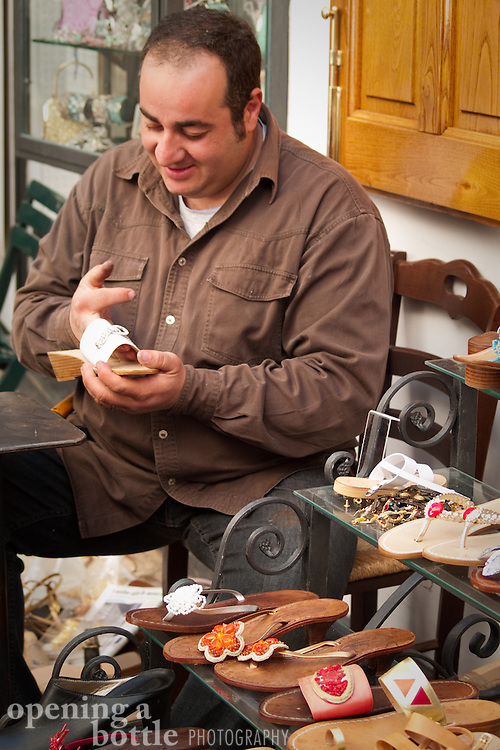 A cobbler works on a shoe, Positano, Italy.