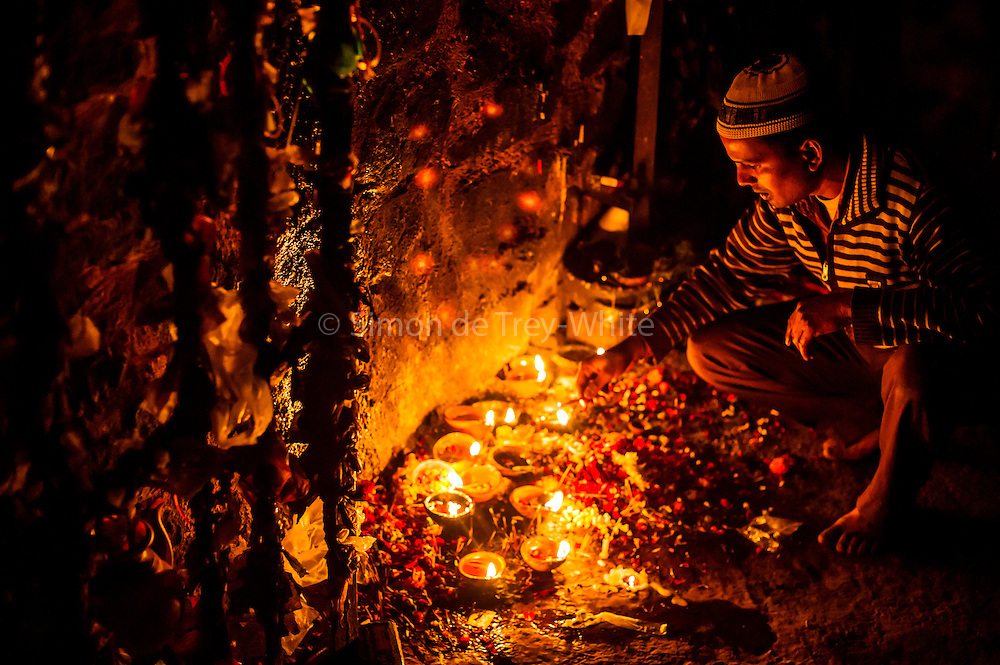 18th December 2014, New Delhi, India. A man lights an incense stick as an  offering as he asks for wishes to be granted by Djinns in the ruins of Feroz Shah Kotla in New Delhi, India on the 18th December 2014<br /> <br /> PHOTOGRAPH BY AND COPYRIGHT OF SIMON DE TREY-WHITE a photographer in delhi<br /> + 91 98103 99809. Email: simon@simondetreywhite.com<br /> <br /> People have been coming to Firoz Shah Kotla to leave written notes and offerings for Djinns in the hopes of getting wishes granted since the late 1970's. Jinn, jann or djinn are supernatural creatures in Islamic mythology as well as pre-Islamic Arabian mythology. They are mentioned frequently in the Quran  and other Islamic texts and inhabit an unseen world called Djinnestan. In Islamic theology jinn are said to be creatures with free will, made from smokeless fire by Allah as humans were made of clay, among other things. According to the Quran, jinn have free will, and Iblis abused this freedom in front of Allah by refusing to bow to Adam when Allah ordered angels and jinn to do so. For disobeying Allah, Iblis was expelled from Paradise and called &quot;Shaytan&quot; (Satan).They are usually invisible to humans, but humans do appear clearly to jinn, as they can possess them. Like humans, jinn will also be judged on the Day of Judgment and will be sent to Paradise or Hell according to their deeds. Feroz Shah Tughlaq (r. 1351&ndash;88), the Sultan of Delhi, established the fortified city of Ferozabad in 1354, as the new capital of the Delhi Sultanate, and included in it the site of the present Feroz Shah Kotla. Kotla literally means fortress or citadel.