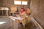 Female carpenter carving name of a coffee shop at  CIQAM-Women Social Enterprise, making carpentry product line at Village Altit, Hunza-Nagar, Gilgit-Baltistan. It is solely run by women carpenters.