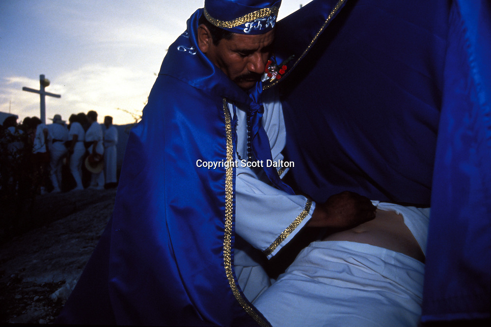 A curandero, or healer, performs a healing ritual in Espinazo, Mexico at a bi-annual gathering of the followers of Nino Fidencio, a famous Mexican healer from the 1930's. Followers of Nino Fidencio believe that some healers become possessed by the spirit of Nino Fidencio and then have his healing powers. Thousands of believers make the pilgrimage each year to pray for miracles or to be healed. His believers, an estimated 20,000, gather in his hometown for a three-day festival twice a year in March and October. (Photo/Scott Dalton)