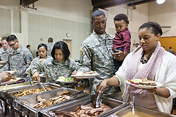Spc Colin Lanhan holds his son Coltin as Mia dishes the food while in line at a Thanksgiving dinner for soldiers of JBLM held in Chris Knutzen hall of the Anderson University center on Wednesday, Nov. 26, 2014. (Photo/John Froschauer)
