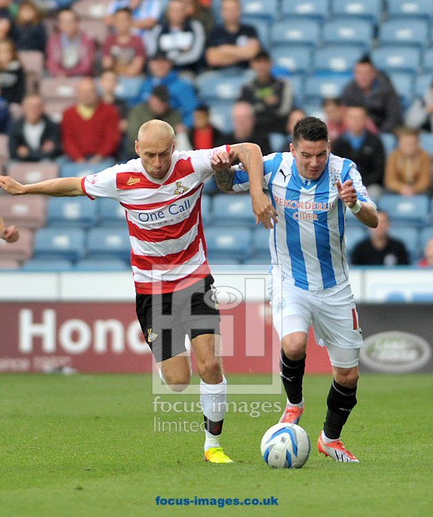 Picture by Graham Crowther/Focus Images Ltd +44 7763 140036<br /> 14/09/2013<br /> Adam Hammill of Huddersfield Townbattles with David Cotterill of Doncaster Rovers during the Sky Bet Championship match at the John Smiths Stadium, Huddersfield.