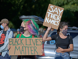 Women hold signs at a June 3, 2020, Black Lives Matter protest in Eugene, Oregon. Participants were protesting the murder of George Floyd and other African-Americans by police.