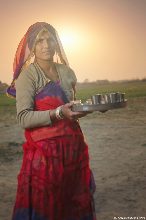 An Indian wife prepares to serve chai to guests in rural Rajasthan where visitors are seldom and farm life can be difficult. Bikaner, Rajasthan, India.