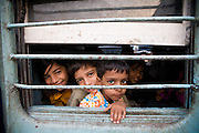 Agra. Curious children look through the window of a train