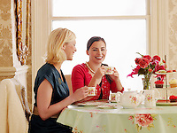 Two young women sitting at dining table drinking tea