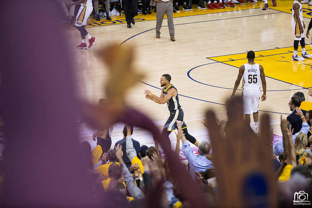 Fans celebrate as Golden State Warriors guard Stephen Curry (30) hits a three pointer against the New Orleans Pelicans at Oracle Arena during Game 2 of the Western Semifinals in Oakland, California, on May 1, 2018. (Stan Olszewski/Special to S.F. Examiner)