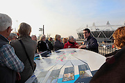 Visitors listen to a tourists guide showing a map of the Olympic Park with in the background the London Olympic Stadium, Populous (formerly HOK Sport), 2011, London, United Kingdom. Picture by Manuel Cohen