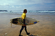 Surfer holding his board walking into the sea Fistral beach Newquay UK May 2002