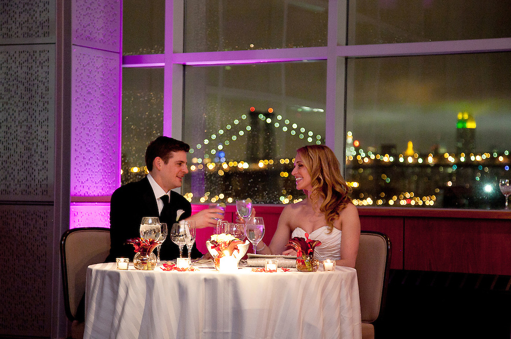 Bride and groom toast each other with champagne by candlelight with Brooklyn Bridge in background