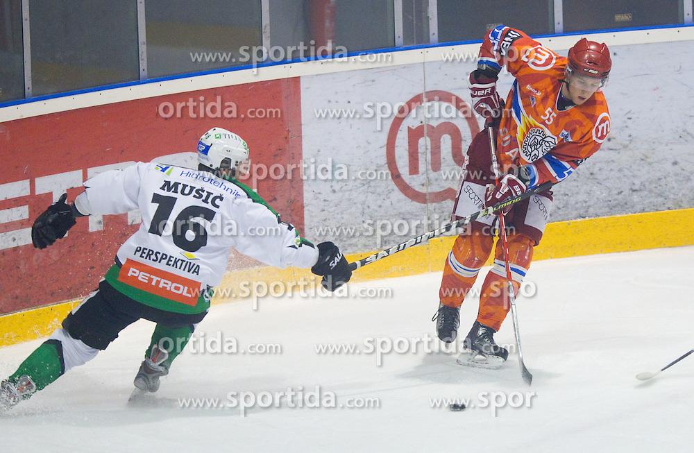 Ales Music of Olimpija vs Robert Sabolic of Jesenice during ice hockey match between HK Acroni Jesenice and  HDD Tilia Olimpija Ljubljana at 33rd Round of EBEL league, on January 1, 2011 in Arena Podmezakla, Jesenice, Slovenia. (Photo By Vid Ponikvar / Sportida.com)