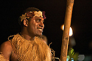 Local man in traditional costume lights torches at Iririki Island Resort in Port Vila, Vanuatu.