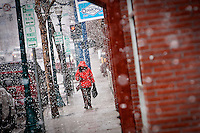 JEROME A. POLLOS/Press..A woman walks in downtown Coeur d'Alene during heavy snowfall Thursday.