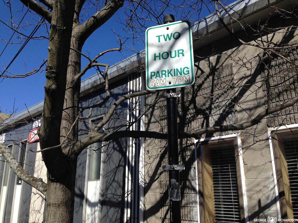 """Lawrence, Massachusetts, 04/05/2016<br /> Señal de transito en Lawrence. El letrero dice """"Parqueo por dos hora"""". Una flecha -en verde- apunta en dirección al espacio reservado.<br /> <br /> En el mismo bloque, a solo 50 pies, una señal similar apuntando en la misma dirección, es 'vandalizada'  con un stiker, colocando encima una """"P"""" - símbolo de parqueo pagado"""" contradiciendo el primer letrero.<br /> <br /> Este no es un caso aislado. La incoherencia y la ambigüedad en las señales de transito y de parking -parqueo- en Lawrence, origina enorme frustración y frecuente violencia verbal entre conductores y oficiales de parking."""