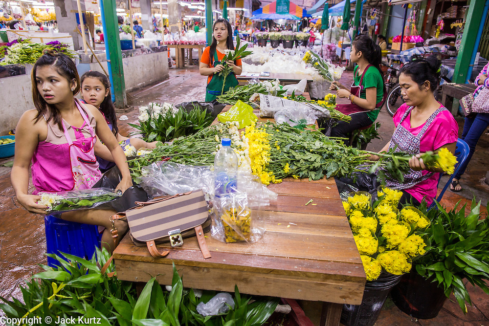 09 OCTOBER 2012 - BANGKOK, THAILAND:  Workers package flowers for sale in the Bangkok Flower Market. The Bangkok Flower Market (Pak Klong Talad) is the biggest wholesale and retail fresh flower market in Bangkok. It is also one of the largest fresh fruit and produce markets in the city. The market is located in the old part of the city, south of Wat Po (Temple of the Reclining Buddha) and the Grand Palace.    PHOTO BY JACK KURTZ