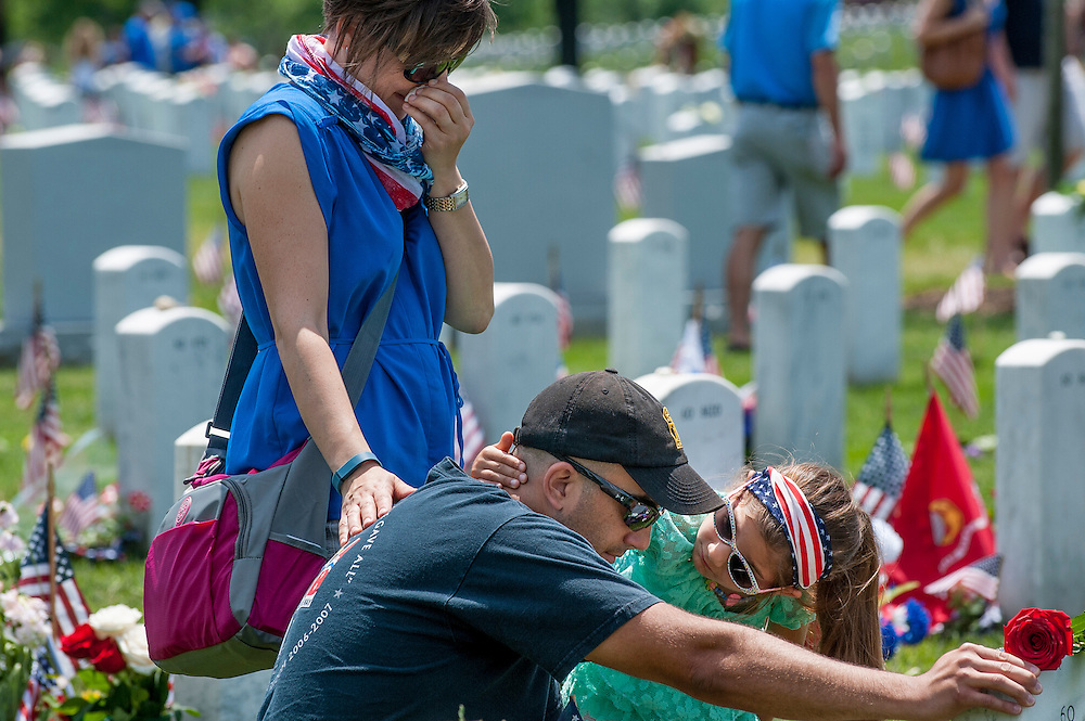On Memorial Day, Major Brian Hansen USA, is comforted by his wife Tina and daughter Isabella as he visits the grave of comrade Henry Link at Arlington National Cemetery in Arlington, Virginia, USA, on 25 May 2015.