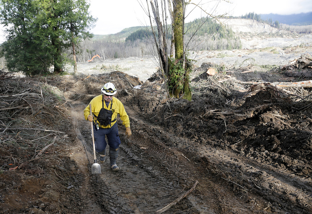 Benton County Fire District 1 Assistant Chief Jack Coats, serving as a task force leader, makes his way up a road on as search work continues in the mud and debris from a massive mudslide that struck Oso near Darrington, Washington April 2, 2014. Efforts to recover bodies following a Washington state mudslide that killed at least 29 people could be hampered in the coming weeks if melting snow runs into a clogged river at the disaster site, officials said. Over the past two days, workers at the mud pile in the foothills of the Cascade Mountains, northeast of Seattle, have taken advantage of sunny skies and receding water, but more rain is expected from Thursday through Sunday.  REUTERS/Jason Redmond (UNITED STATES)