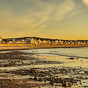 I was fortunate to capture the perfect morning light at low tide on Cape Ann in Gloucester, MA.  I've taken certain liberties in the post processing to get the most out of this shot and have several presentations available.<br /> <br /> In each, you can see the rocky shore made visible by the receding tide as well as the beautiful sky casting its glow over the shore and houses.