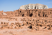 Admire fanciful hoodoos, mushroom shapes, and rock pinnacles in Goblin Valley State Park, in Emery County between the towns of Green River and Hanksville, in central Utah, USA. The Goblin rocks eroded from Entrada Sandstone, which is comprised of alternating layers of sandstone (cross-bedded by former tides), siltstone, and shale debris which were eroded from former highlands and redeposited in beds on a former tidal flat. As part of the Colorado Plateau, the San Rafael Swell is a giant dome-shaped anticline of rock (160-175 million years old) that was pushed up during the Paleocene Laramide Orogeny 60-40 million years ago. Since then, infrequent but powerful flash floods have eroded the sedimentary rocks into valleys, canyons, gorges, mesas, and buttes.