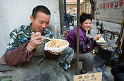 Chinese market vendors eat noodles for lunch in a Xining in China's western Qinghai Province.