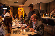 New York, NY, Sept. 30, 2013. Grant Reynolds, wine director at Charlie Bird, serving a Montevitrano Agliancio to patron Leon Rossi and Laura Fuentes.