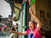 05 JANUARY 2014 - BANGKOK, THAILAND:  A shopkeeper encourages anti-government protestors who walked past her foodshop during an anti-government march in Bangkok. Suthep Thaugsuband, leader of the anti-government protests in Bangkok, led the protestors on a march through the Chinatown district of Bangkok. Tens of thousands of people waving Thai flags and blowing whistles gridlocked what was already one of the most congested parts of the city. The march was intended to be a warm up to their plan by protestors to completely shut down Bangkok starting Jan. 13.    PHOTO BY JACK KURTZ